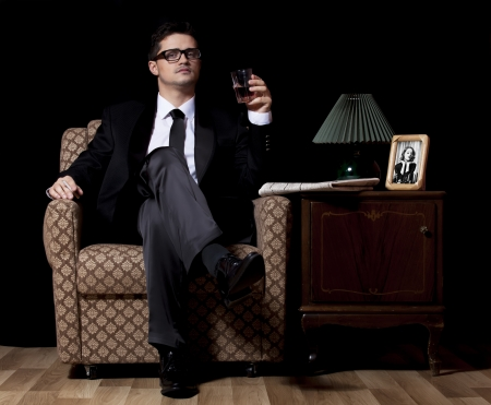 desperado: Man with alcohol sitting in vintage armchair Stock Photo