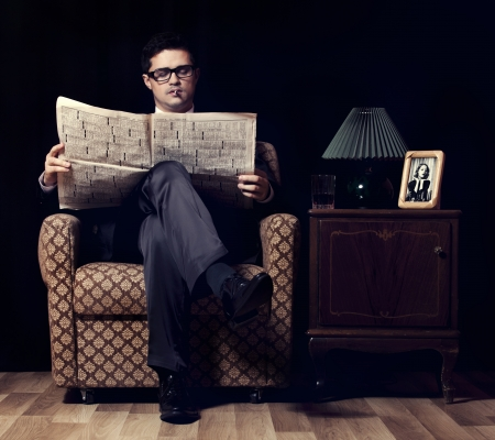 Man with newspaper sitting in vintage armchair photo