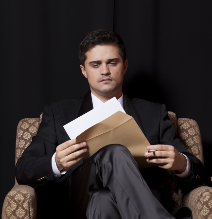 Man with file sitting in vintage armchair photo