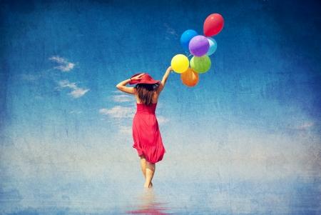 color in: Chica morena con globos de colores en la costa. Fotos en estilo antiguo color de la imagen. Foto de archivo
