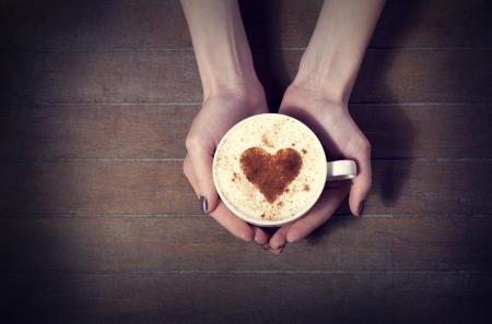 mujer tomando cafe: mujer que sostiene la taza de caf� caliente, con forma de coraz�n