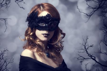 masked woman: Mujeres hermosas en la m�scara de carnaval. Foto de bosque en el fondo.