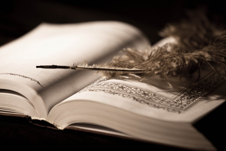 well read: Pen on old book. Photo in old vintage style Stock Photo