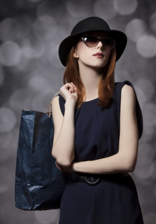 Style redhead girl with shopping bag photo