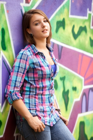 Style teen girl standing near graffiti wall.