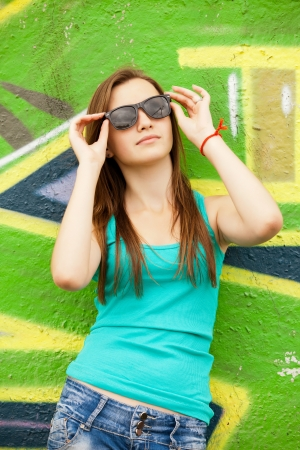 Style teen girl in sunglasses near graffiti background. photo