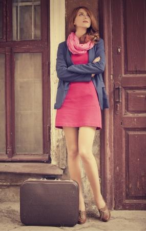 mujer con maleta: retrato de una bella joven en la calle en estilo vintage