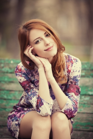 Style redhead girl sitting on the bench  Stock Photo