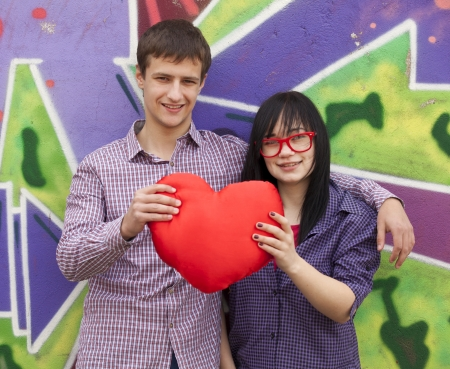 Teens with heart near graffiti wall. photo
