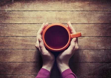 mujer tomando cafe: Mujer que sostiene la taza de t� caliente