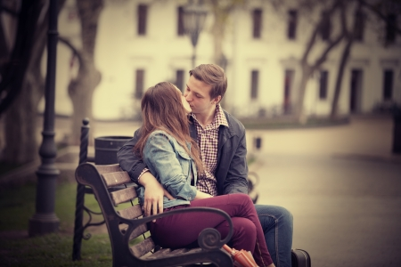 french kiss: Couple kissing at the bench at alley.