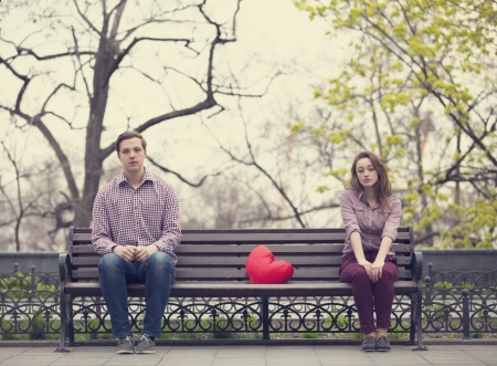 Sad teens sitting at the bench at the park photo