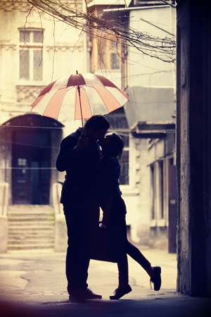 woman with umbrella: Couple kissing at patio Stock Photo