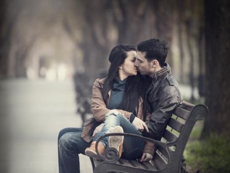 baiser amoureux: Couple s'embrassant sur le banc � alley. Banque d'images