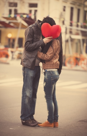Young couple with shape heart kissing on the street photo