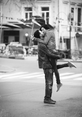french kiss: Young couple kissing on the street