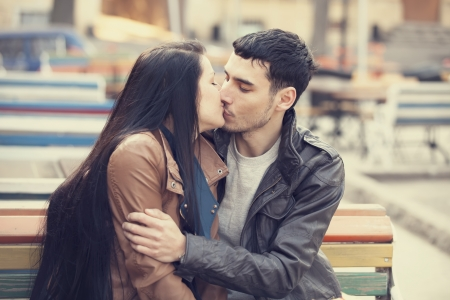 pareja adolescente: Pareja bes�ndose en el banco en el callej�n.
