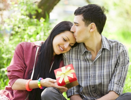 Couple with gift at green grass in the park photo