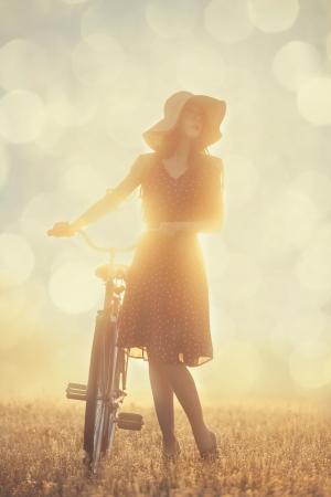 bicicleta retro: Chica y en bicicleta en el campo en tiempo de la salida del sol
