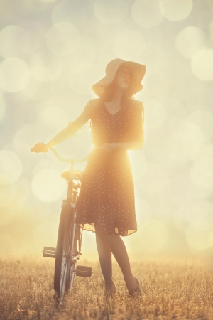 field sunset: Girl and on a bike in the countryside in sunrise time Stock Photo