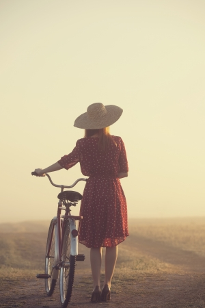 Girl on a bike in the countryside in sunrise time. Stock Photo - 19430956