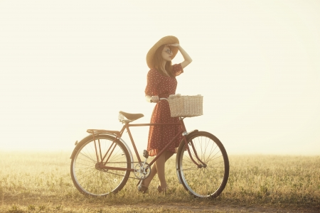 Girl on a bike in the countryside in sunrise time. Stock Photo - 19430880