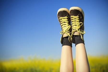dirty feet: baskets vintage de repos sur fond bleu ciel et sur le terrain rapseed Banque d'images