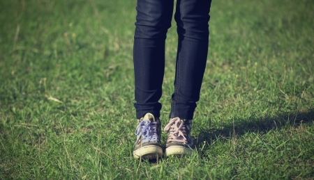Girl in vintage sneakers resting on the grass photo
