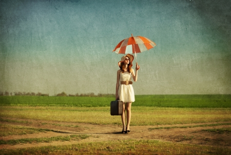 Redhead enchantress with umbrella and suitcase at spring countryside. photo