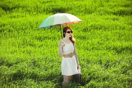 enchantress: Redhead enchantress with umbrella and suitcase at spring countryside