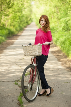 Girl with a bike in the countryside alley photo
