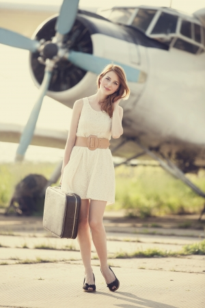 Lonely girl with suitcase at near airplane. Photo in old image style. photo