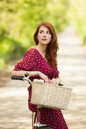 Beautiful girl with bike at countryside. Vintage. photo