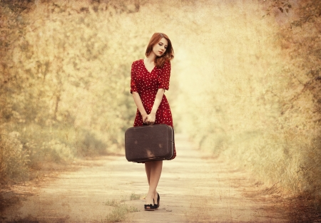 Redhead girl with suitcase at trees alley. photo