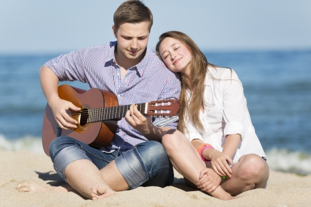 Portrait of young man with guitar and woman on a beach. photo