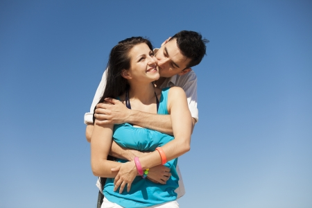 couple cuddling: Beautiful couple kissing on blue sky background. Stock Photo