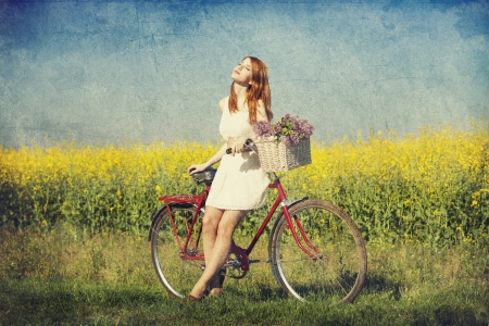 spring fashion: Girl on a bike in the countryside.