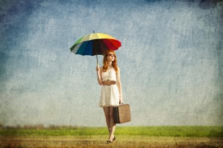 enchantress: Redhead enchantress with umbrella and suitcase at spring countryside. Stock Photo