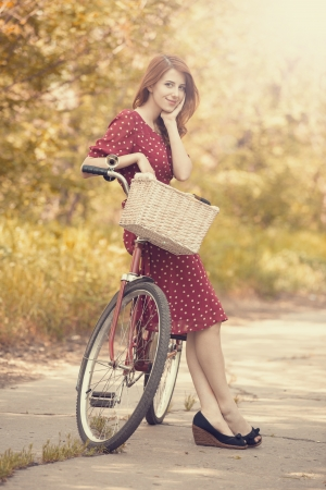 Beautiful girl with bike at countryside. Vintage.