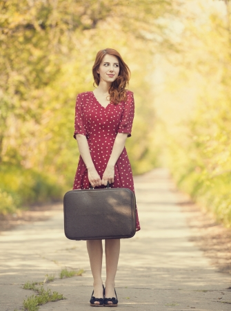 country girls: Redhead girl with suitcase at trees alley. Stock Photo