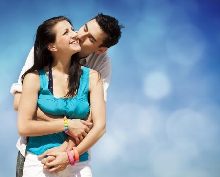 novios besandose: Hermosa pareja bes�ndose en el fondo del cielo azul. Foto con bokeh en el fondo