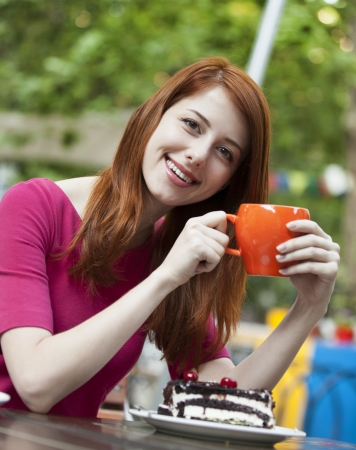 Style redhead girl with cake and cup sitting on the bench in the cafe photo