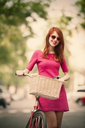 Redhead girl with bike on the street photo
