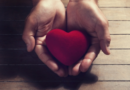 Heart in the hands. On wood background. photo