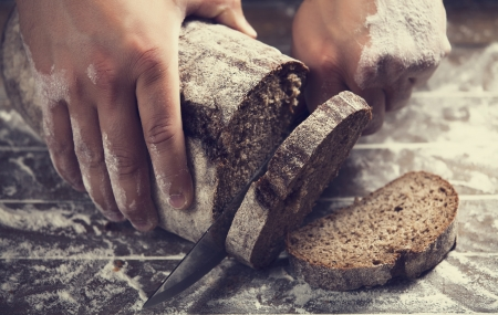 artisanal: Male hands slicing home-made bread