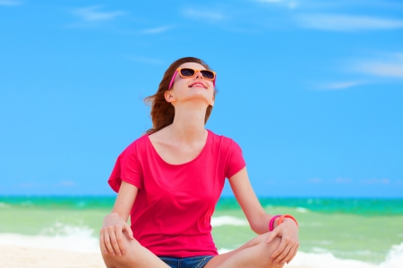 Funny teen girl sitting on the sand at the beach. photo