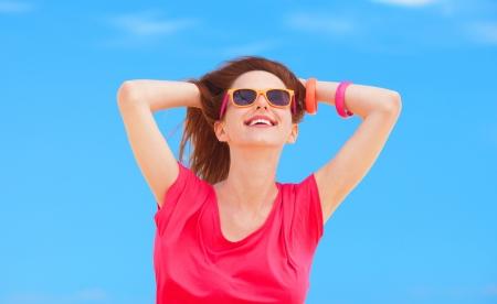 Redhead teen girl on blue sky background photo