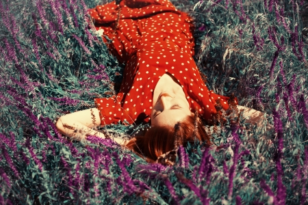 Girl lying on spring grass and flowers. Photo in 40-s cinema colour style. photo