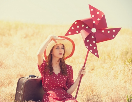 Redhead girl with suitcase and wind turbine sitting at grass photo