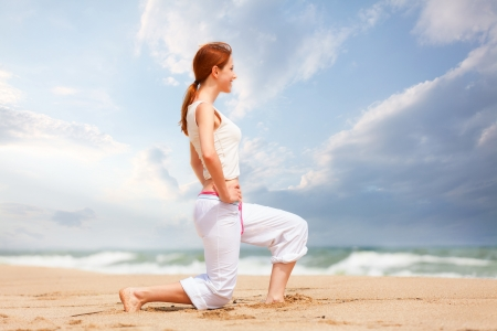 athletic woman performing an exercise in an sand beach photo